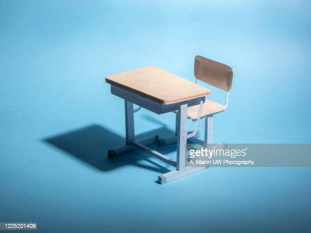 empty school desk on a blue background. conceptual. - 教育 ストックフォトと画像