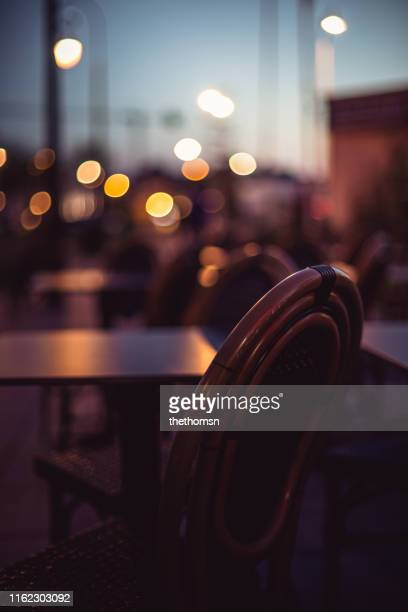 empty seat at outdoor area of restaurant during dawn - focus on foreground stock pictures, royalty-free photos & images