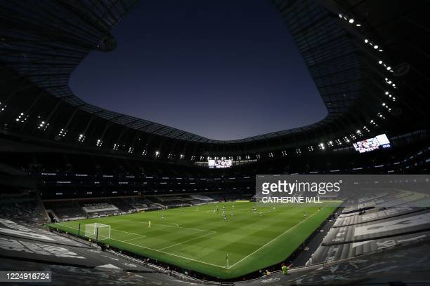 Empty seats and stands are pictured at dusk during the English Premier League football match between Tottenham Hotspur and Everton at Tottenham...