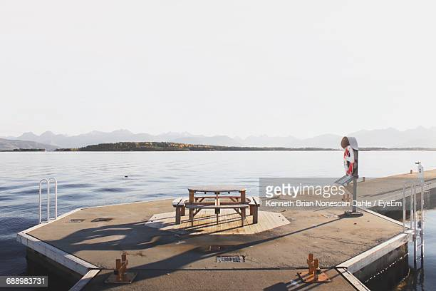 Empty Seats And Table On Pier At Lake Against Clear Sky