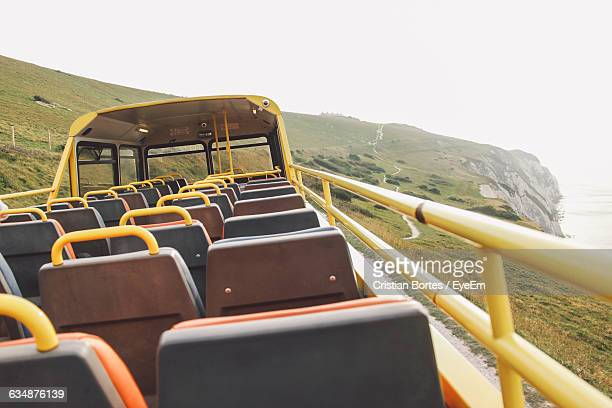 empty seats in bus against sky on field - bortes stockfoto's en -beelden