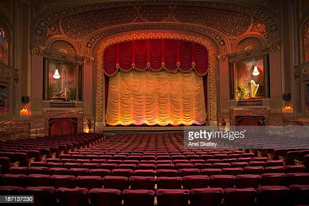 empty seats in ornate movie theater - stage curtain stock pictures, royalty-free photos & images