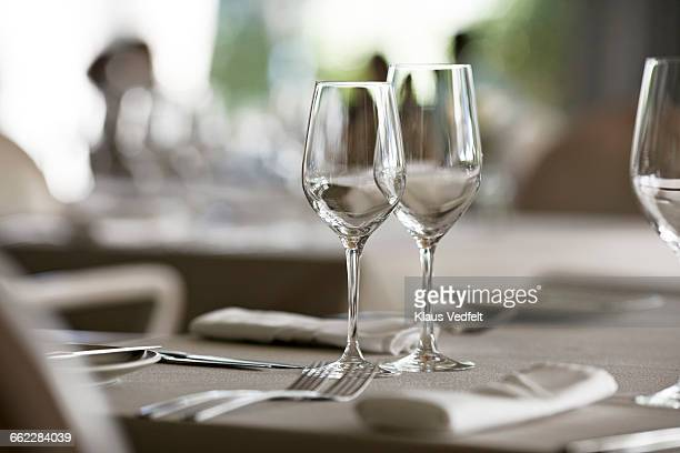 Empty set table at fine restaurant, guests in back