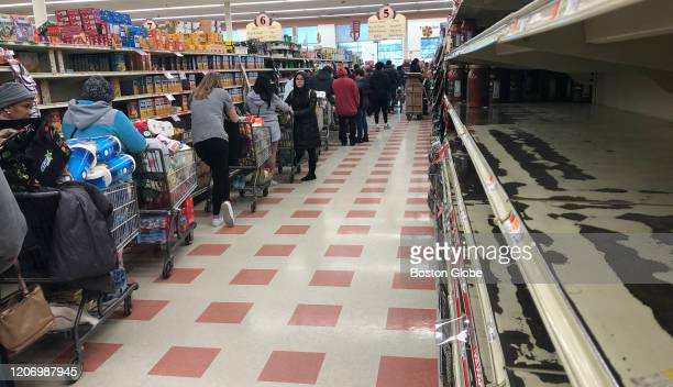 Empty shelves and a line of shoppers waiting to checkout stretching to the back of the store at Market Basket in Chelsea MA as coronavirus concerns...
