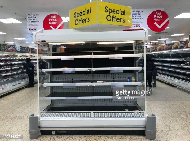 Empty shelves are pictured inside a Tesco supermarket store in Liverpool, north west England on March 19, 2020. - Britain's supermarkets on Wednesday...