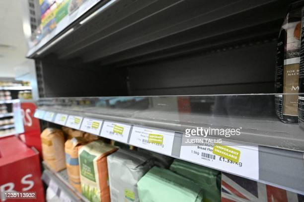 Empty shelves are pictured where packets of flour should be stocked, inside a Waitrose supermarket in London on September 7, 2021. - Sparse shelves...