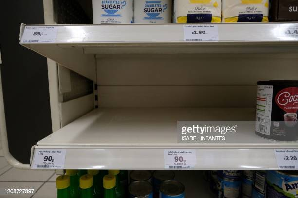 Empty shelves where packets of flour would normally be stocked are pictured below half-empty egg, and sugar stocks, inside a Sainsbury's supermarket...