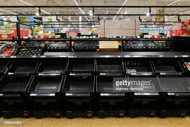 Empty shelves where tomatoes were being sold at an ASDA store on July 21, 2021 in Cardiff, United Kingdom. Supermarkets across the UK are emptying of...