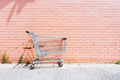 Empty shopping cart against a pink brick wall - gettyimageskorea