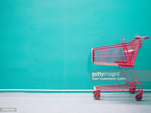 empty shopping cart against turquoise colored wall - shopping cart stock pictures, royalty-free photos & images
