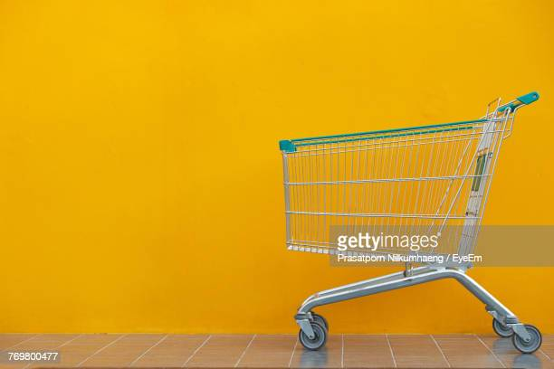 Empty Shopping Cart Against Yellow Wall
