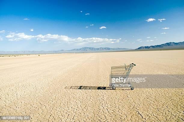 empty shopping cart in desert - lake bed stock-fotos und bilder