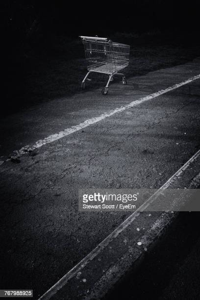Empty Shopping Cart On Road At Night
