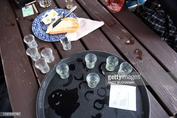 Empty shot glasses are pictured at an outside table as customers enjoy drinks at a re-opened Wetherspoons pub in Glasgow on April 26, 2021 following...