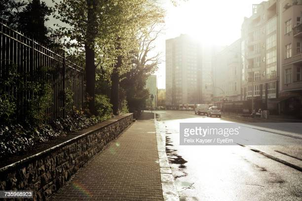 empty sidewalk in city on sunny day - bagnato foto e immagini stock