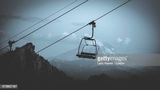 Empty Ski Lift Hanging By Snow Covered Mountains Against Sky At Dusk