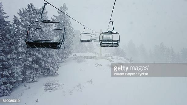 Empty Ski Lifts Over Snow Covered Field