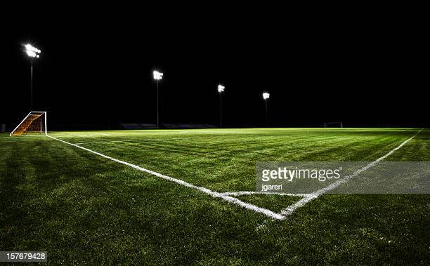 Empty soccer field at night with stadium lights on