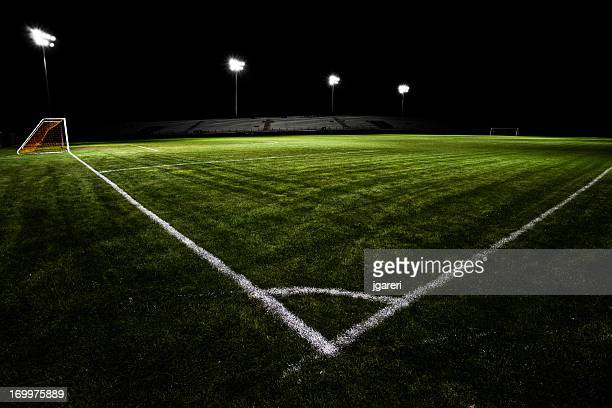Empty soccer field with floodlights at night