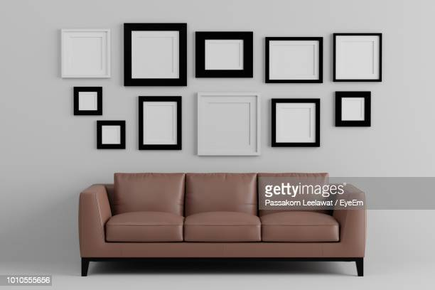 empty sofa against picture frames on wall at home - picture frame stock pictures, royalty-free photos & images