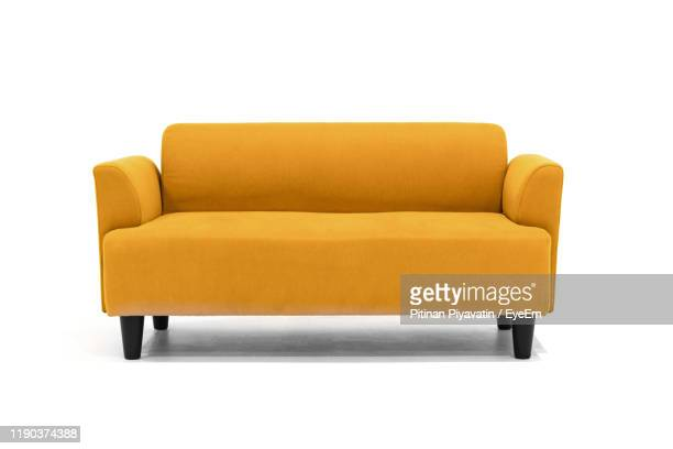 empty sofa against white background - sofa stock-fotos und bilder