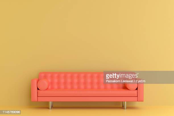 empty sofa against yellow background - sofa stock-fotos und bilder
