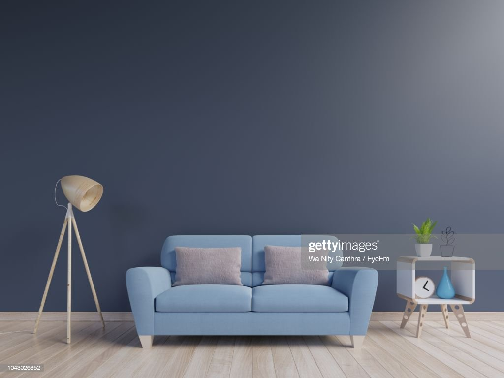 Empty Sofa By Lamp On Hardwood Floor Against Blue Wall : ストックフォト