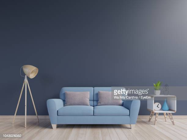 empty sofa by lamp on hardwood floor against blue wall - sofa stock-fotos und bilder