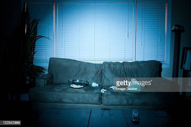 empty sofa with box of tissues and popcorn - blue film video stock photos and pictures