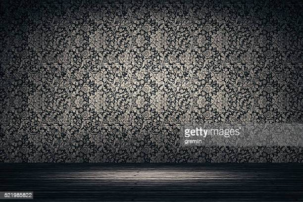 Empty spotlit room with flower pattern wallpaper