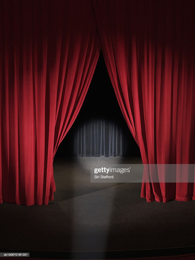 Empty stage with curtains slightly open and spotlight on : Stock Photo