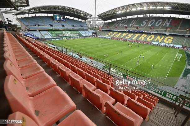 Empty stands are seen while football players warm up on the ground prior to the opening game of South Korea's KLeague football match between Jeonbuk...