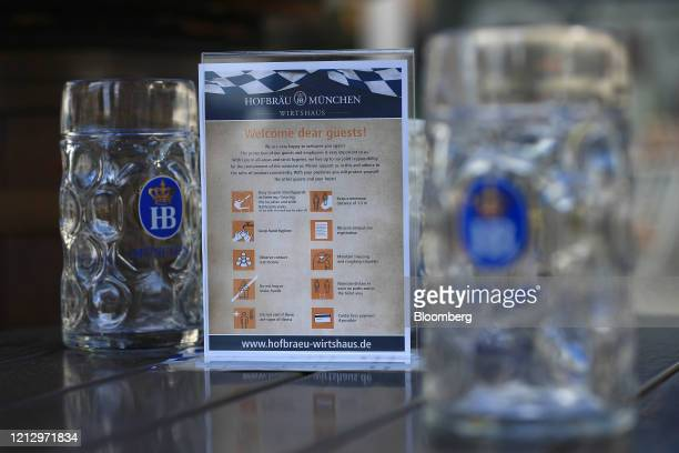 Empty stein glasses sit beside a social distancing and hygiene information sign outside a Bavarian-themed beer hall ahead of reopening in Berlin,...