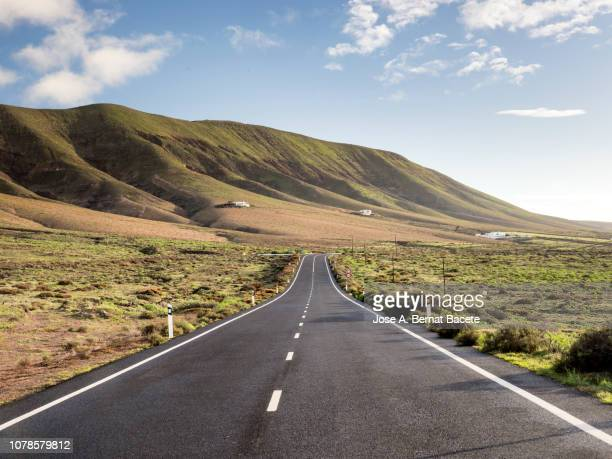 empty straight road that crosses a zone of volcanic coast. lanzarote, canary islands, spain. - long stock pictures, royalty-free photos & images