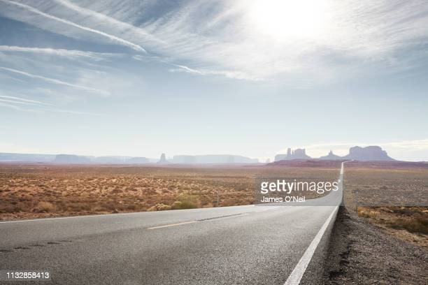 empty straight road with distant cliffs - nature stock pictures, royalty-free photos & images