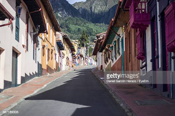 empty street amidst houses leading towards mountain - bogota stock pictures, royalty-free photos & images
