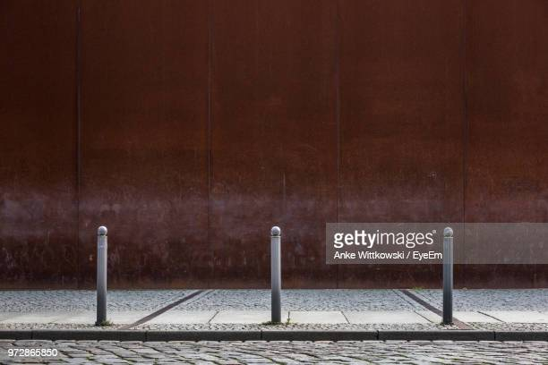 empty street and footpath against wall - street stockfoto's en -beelden