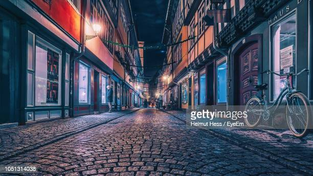 empty street in illuminated city at night - westeuropa stock-fotos und bilder