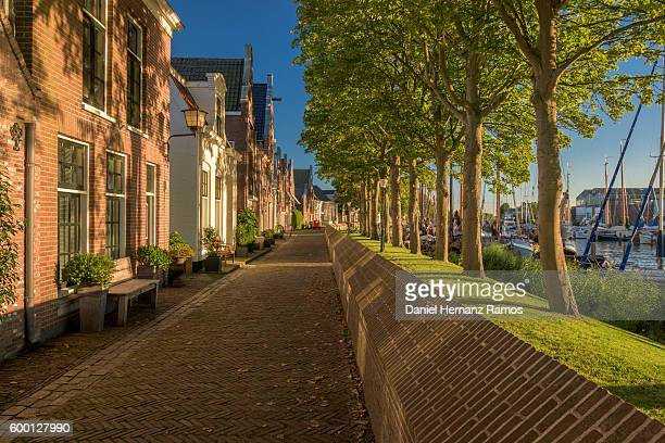 empty street in muiden at sunset with typical dutch houses on the left and a harbour on the right. the netherlands - village stock pictures, royalty-free photos & images