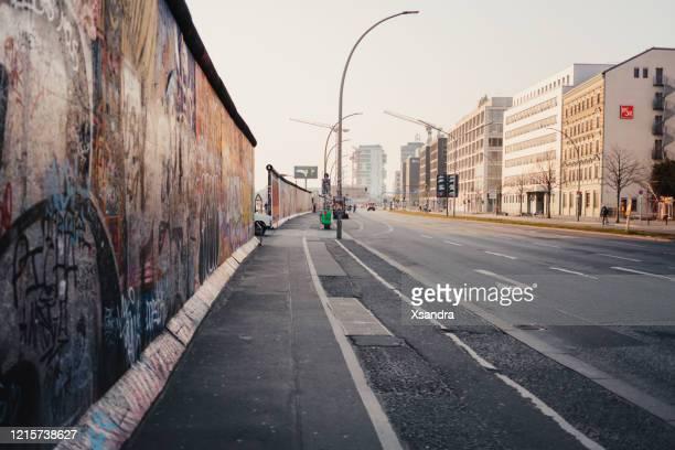 leere straße in der nähe der east side gallery in berlin während der covid-19-sperrung - freie straße stock-fotos und bilder