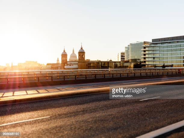 empty street of london at sunset with the city skyline behind - london bridge stock pictures, royalty-free photos & images