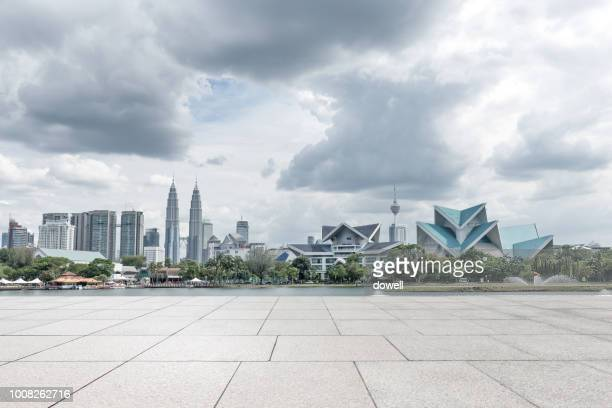 empty street with skyline of kuala lumpur - kuala lumpur stock pictures, royalty-free photos & images