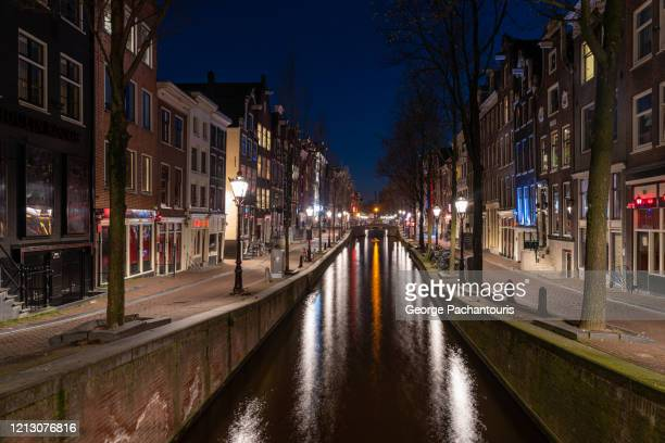 empty streets and shops in the red light district in amsterdam - amsterdam stock pictures, royalty-free photos & images