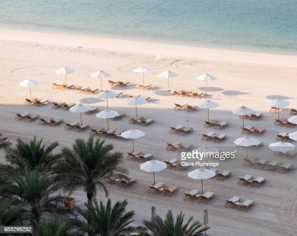 Empty sun loungers and parasols on a beach early in the morning, taken from a high view.