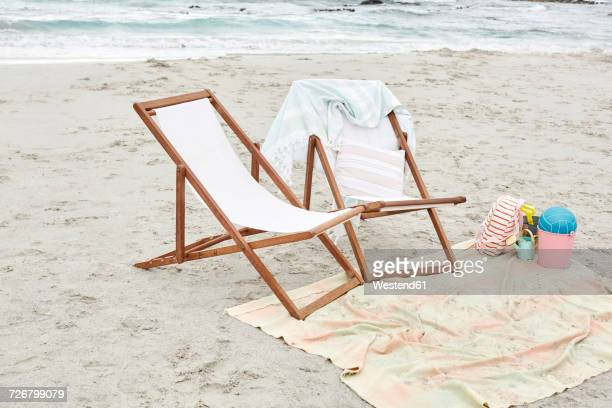 Empty sun loungers on the beach with towels and toys