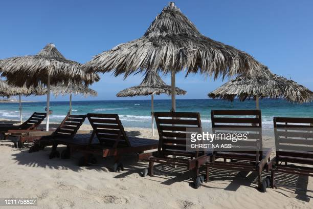 Empty sunbeds lie along a beach in the Cypriot resort town of Ayia Napa on May 4 as the island country gradually eases lockdown restrictions placed...