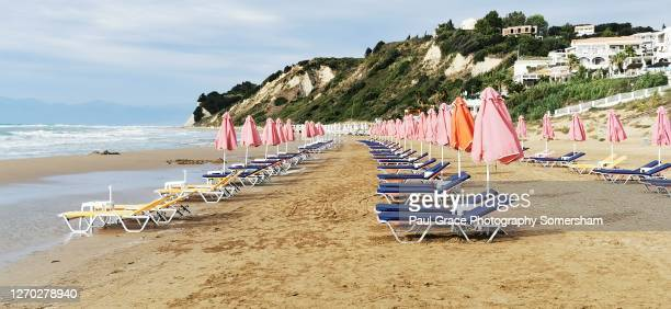 empty sunbeds on the greek island of corfu - greece stock pictures, royalty-free photos & images