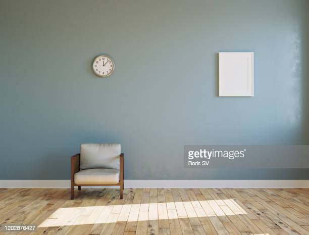 empty sunlit room with armchair and clock on the wall - leer stock-fotos und bilder