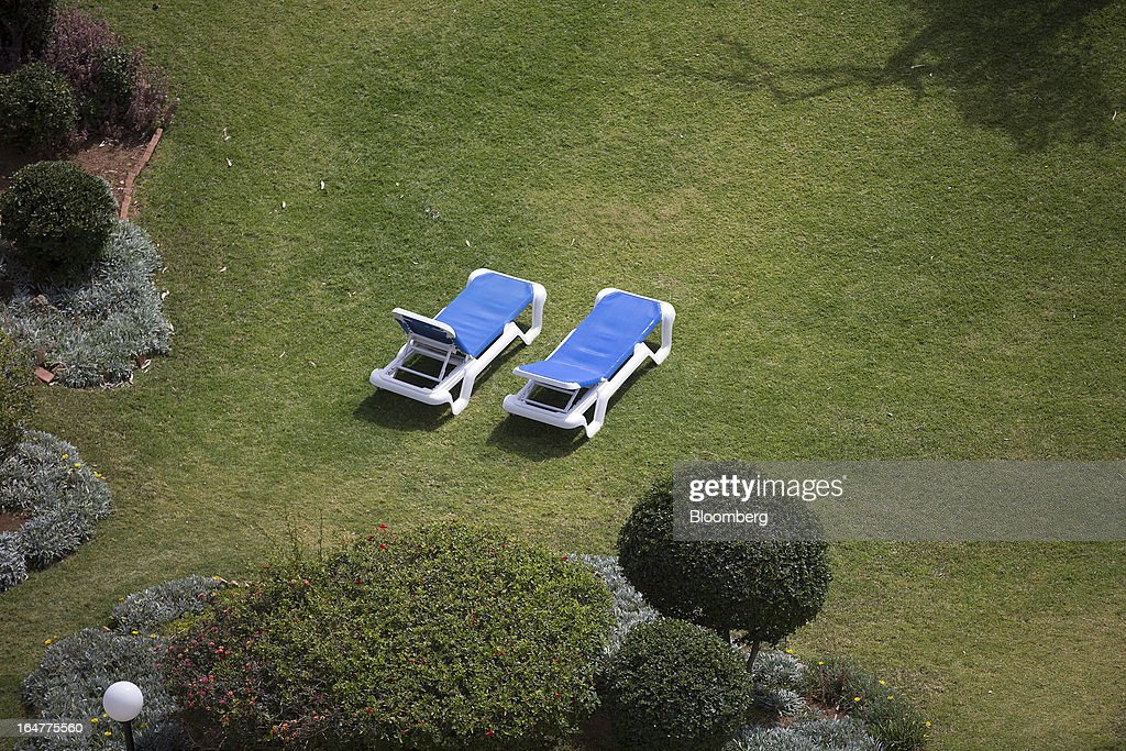 Empty sunloungers are seen in the grounds of the luxury five star St Raphael resort hotel in Limassol, Cyprus, on Wednesday, March 27, 2013. Directly or indirectly, tourism makes up a quarter of Cyprus's economy with visitors from the two main tourism markets, Germany and U.K. Photographer: Simon Dawson/Bloomberg