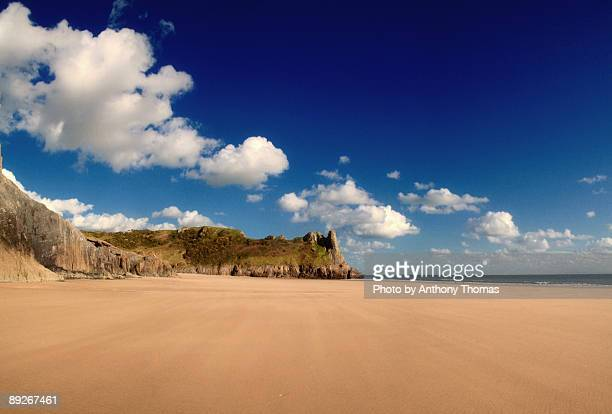 empty  sunny beach - swansea stock photos and pictures